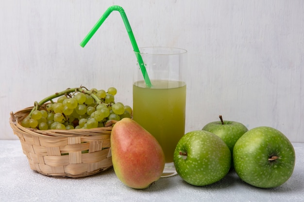 Vooraanzicht groene druiven in een mand met peer groene appels en appelsap met een groen rietje in een glas op een witte achtergrond