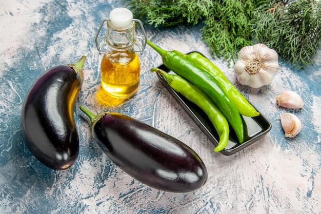 Vooraanzicht groene hete pepers op zwarte plaat aubergines knoflookolie pepers op blauw-witte achtergrond