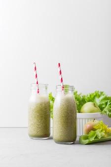 Vooraanzicht groene smoothie flessen met kopie ruimte