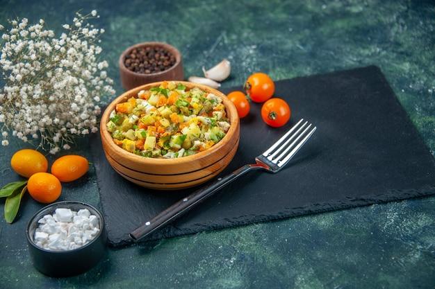 Vooraanzicht groentesalade van gekookte ingrediënten in plaatje op donkere achtergrond