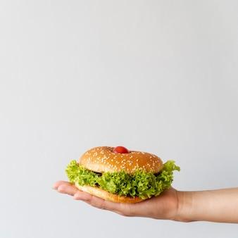 Vooraanzicht hamburger gehouden door persoon