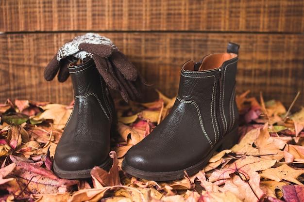 Vooraanzicht handschoenen en laarzen op de top van bladeren