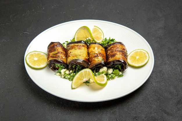 Vooraanzicht hartige auberginerolletjes met schijfjes citroen op een donkere ondergrond koken maaltijd diner citrusolie schotel