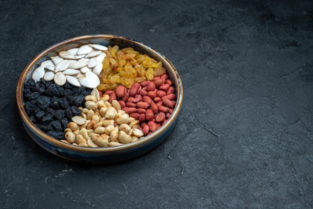 Vooraanzicht hazelnoten en rozijnen en andere noten op donkergrijs oppervlak