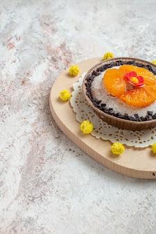 Vooraanzicht heerlijk cakedessert met gesneden mandarijnen op de witte ruimte