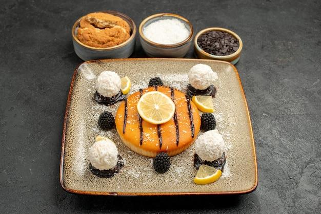 Vooraanzicht heerlijk cakedessert met kokossnoepjes op een donkere achtergrond taartdessert zoete cake snoepthee
