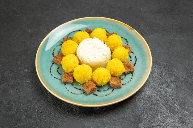 Vooraanzicht heerlijk dessert kleine gele snoepjes met cake in plaat op de grijze achtergrond snoep thee suiker cake zoet