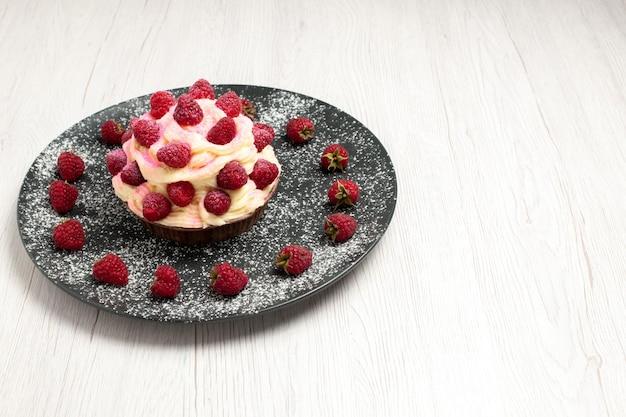 Vooraanzicht heerlijk fruitcake-roomdessert met frambozen op een witte achtergrond, zoete roomthee-dessert, biscuittaarttaart