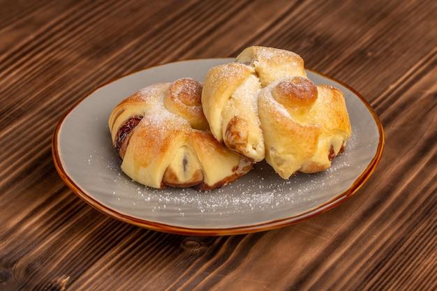 Vooraanzicht heerlijk gebak met vulling binnen plaat op de houten tafel, zoete suiker cake bakken gebak fruit
