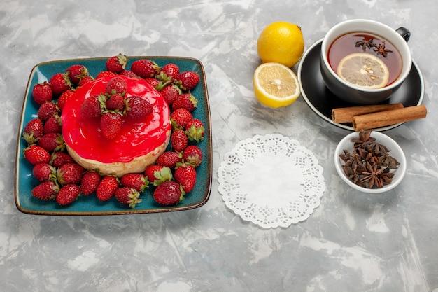 Vooraanzicht heerlijk uitziende cake kleine taart met kopje thee en verse aardbeien op witte ondergrond