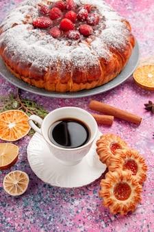 Vooraanzicht heerlijke aardbeientaart gebakken met suikerpoeder koekjes en thee op lichtroze oppervlakte cake zoete suiker biscuit koekjes taart