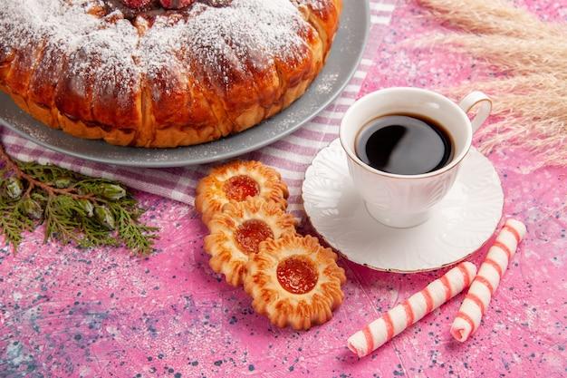 Vooraanzicht heerlijke aardbeientaart suiker gepoederd met kopje thee en koekjes op lichtroze ondergrond cake zoete koekje koekjesthee