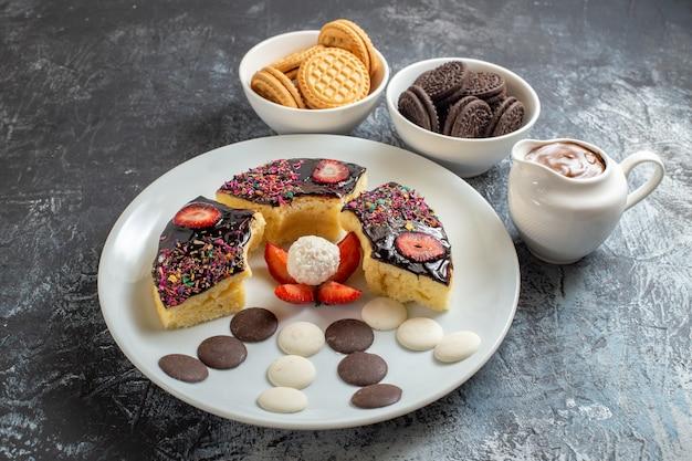 Vooraanzicht heerlijke cakeplakken met koekjes op de donkere achtergrond