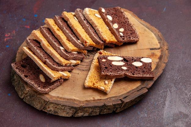Vooraanzicht heerlijke cakeplakken met noten op donkere ruimte