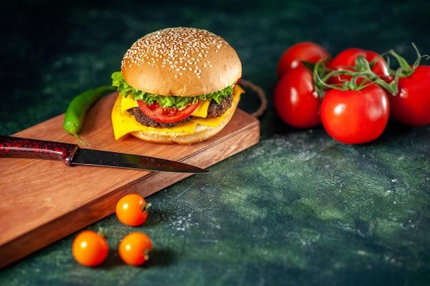 Vooraanzicht heerlijke cheeseburger op donkere achtergrond