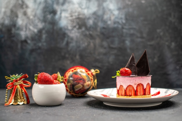 Vooraanzicht heerlijke cheesecake met aardbei en chocolade op ovale schaal met aardbeien kerstspeelgoed