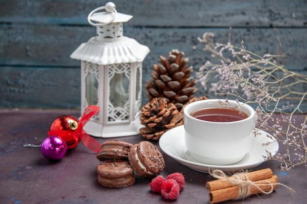 Vooraanzicht heerlijke chocoladekoekjes met kopje thee op het donkere taartkoekje als zoete theekoekje als achtergrond