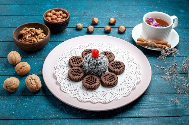 Vooraanzicht heerlijke chocoladekoekjes met noten en kopje thee op de blauwe rustieke suiker van het de theekoekje van het bureauboekje
