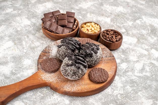 Vooraanzicht heerlijke chocoladetaarten met koekjes en noten op witte ruimte