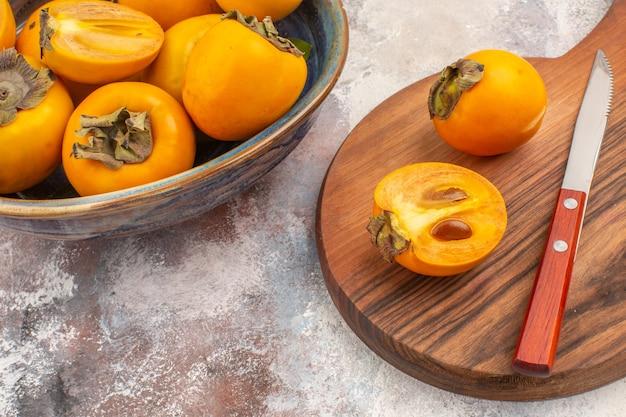 Vooraanzicht heerlijke dadelpruimen in een kom persimmon en mes op snijplank op naakte achtergrond