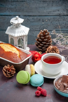 Vooraanzicht heerlijke franse macarons met chocolade en kopje thee op donkere achtergrond taart biscuit zoete thee cake cookie
