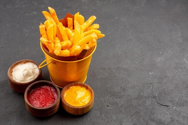 Vooraanzicht heerlijke frietjes met kruiden op donkere ruimte