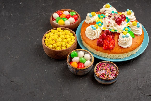 Vooraanzicht heerlijke fruittaart met snoepjes op donkere ruimte