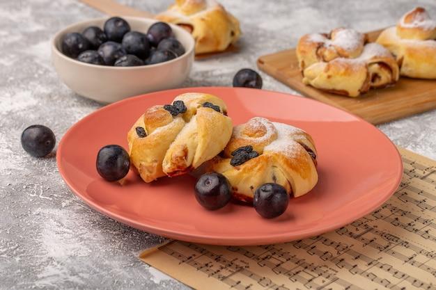 Vooraanzicht heerlijke gebakjes met vulling binnen plaat samen met verse sleedoorns op witte tafel, zoete cake bakken gebak