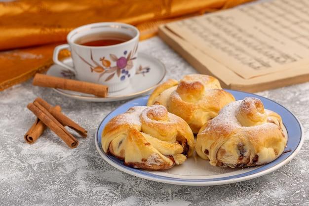Vooraanzicht heerlijke gebakjes met vulling binnenkant plaat samen met thee en kaneel op witte tafel, zoete suiker cake bakken gebak fruit