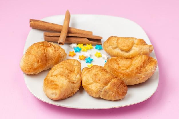 Vooraanzicht heerlijke gebakken croissants met fruit binnen vulling met kaneel snoepjes op de roze achtergrond