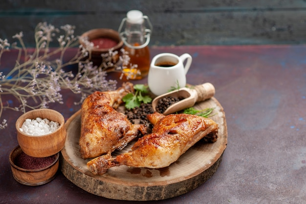 Vooraanzicht heerlijke gebraden kip met verschillende kruiden op donkere ruimte