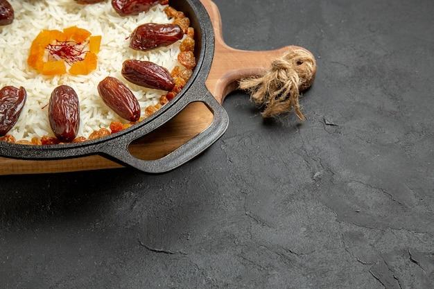 Vooraanzicht heerlijke gekookte plov rijstmaaltijd met khurma en rozijnen op het grijze oppervlak plov rijstschotel maaltijd koken