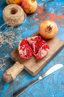 Vooraanzicht heerlijke granaatappels op snijplank diner mes stro draad op blauwe abstract