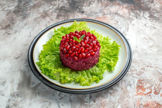 Vooraanzicht heerlijke granaatappelsalade rond gevormd op groene salade op de lichte achtergrond