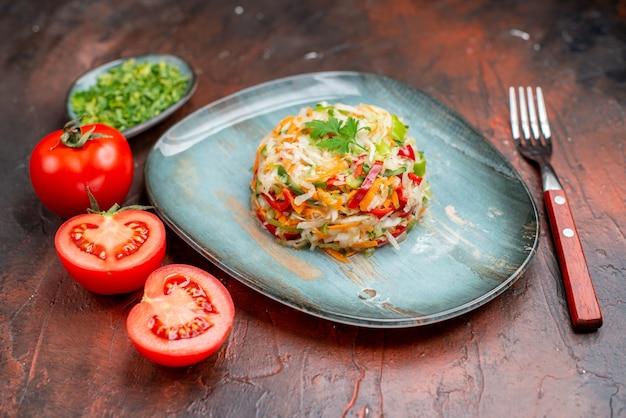 Vooraanzicht heerlijke groentesalade met greens en tomaten op donkere kleur rijp gezond leven fotomaaltijdvoedsel