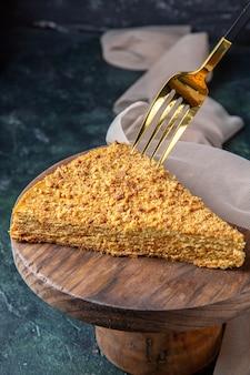 Vooraanzicht heerlijke honingcake plak ervan op een ronde houten plank donkere ondergrond
