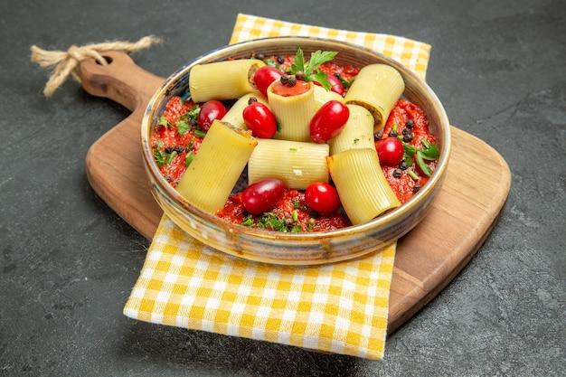 Vooraanzicht heerlijke italiaanse deegwaren met vlees en tomatensaus op grijze achtergrond het deeg van het het voedseldiner van de maaltijddeegwaren