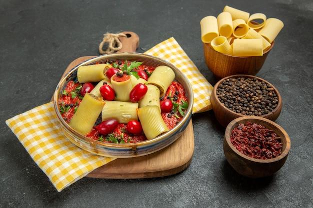 Vooraanzicht heerlijke italiaanse deegwaren met vlees en tomatensaus op het grijze voedsel van het het dinerdeeg van achtergrondmaaltijddeegwaren