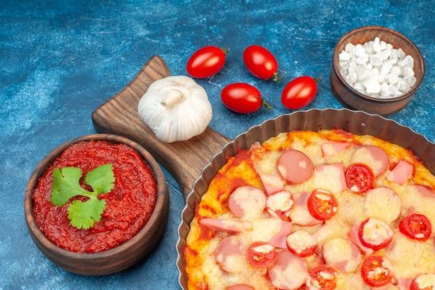 Vooraanzicht heerlijke kaaspizza met worstjes en tomaten op blauwe italiaanse deegcake fastfood fotokleur