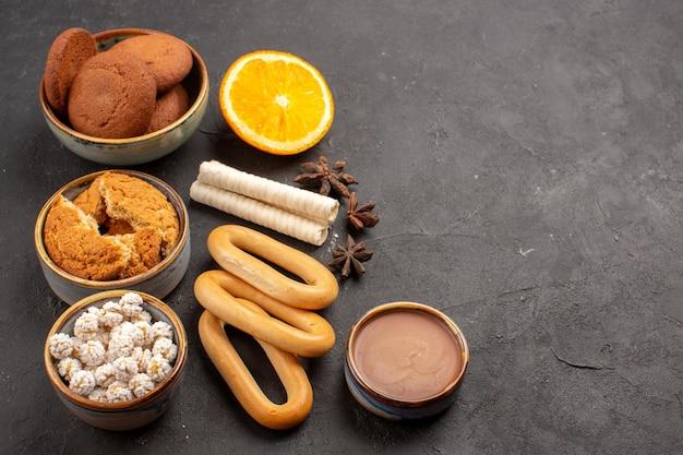 Vooraanzicht heerlijke koekjes met crackers op donkere achtergrond cookie biscuit suiker dessert zoete cake