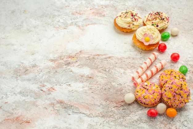 Vooraanzicht heerlijke koekjescakes met kleurrijk suikergoed op witte achtergrondcake, koekjeskoekjestaartkleur