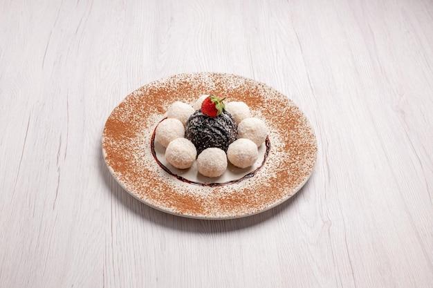Vooraanzicht heerlijke kokossnoepjes met chocoladetaart op witruimte