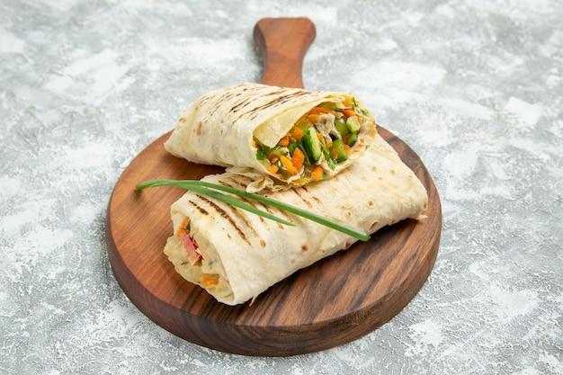 Vooraanzicht heerlijke maaltijd een sandwich gemaakt van vlees gegrild aan het spit gesneden op witte ruimte