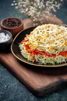Vooraanzicht heerlijke mimosa salade binnen plaat met rode tomaten op donkerblauwe ondergrond maaltijd keuken foto voedsel vakantie verjaardag vlees keuken