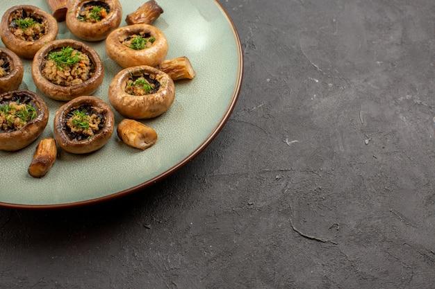 Vooraanzicht heerlijke paddenstoelenmaaltijd gekookt met greens op donkere bureauschotel dinermaaltijd kookpaddestoel