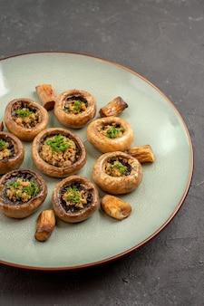 Vooraanzicht heerlijke paddestoelenmaaltijd gekookt met greens op de donkere achtergrondschotel dinermaaltijd kokende paddestoel