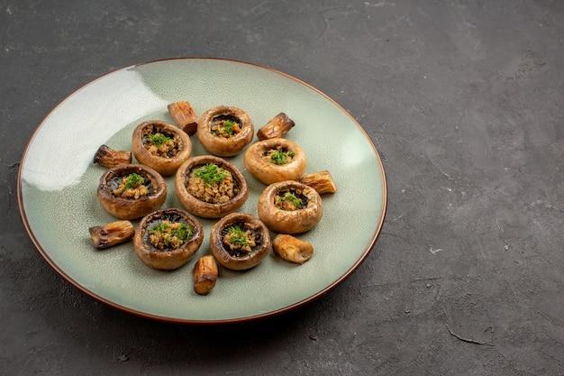 Vooraanzicht heerlijke paddestoelenmaaltijd gekookt met greens op donkere achtergrondschotel dinermaaltijd kokende paddestoelen