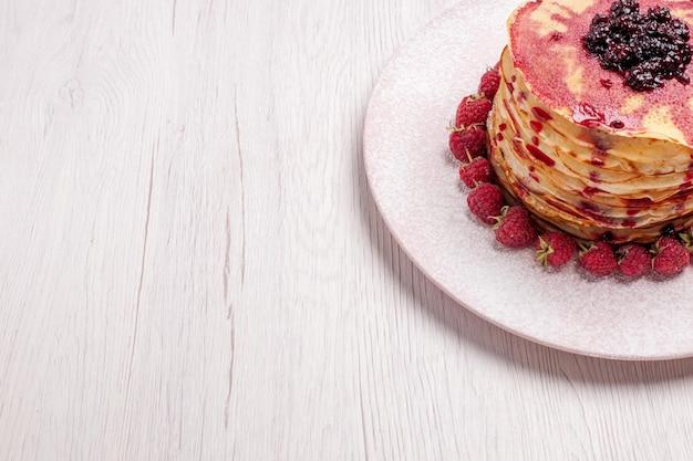 Vooraanzicht heerlijke pannenkoeken met aardbeien en gelei op licht wit bureautaartkoekje, zoete bessenfruitcake