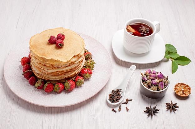 Vooraanzicht heerlijke pannenkoeken met aardbeien en kopje thee op witruimte