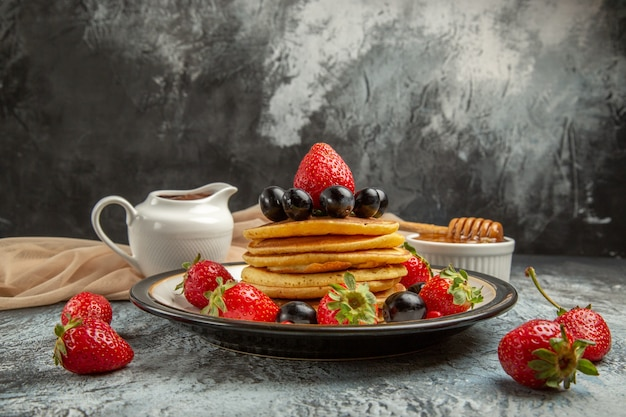 Vooraanzicht heerlijke pannenkoeken met honing en fruit op lichte oppervlakte zoete cakevruchten